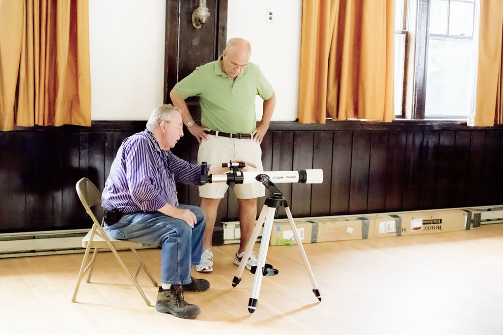 John Root (seated) offers instruction to a new telescope owner